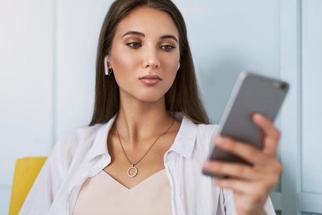 真面目なビジネスウーマンの肖像画、彼女の手にスマートフォンを持って、仕事のために電話を使用しています。