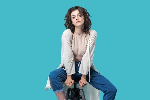 Портрет серьезной спокойной красивой молодой женщины брюнетки в непринужденном стиле, сидящей на стуле и смотрящей в камеру с серьезным лицом. крытая студия выстрел, изолированные на синем фоне.