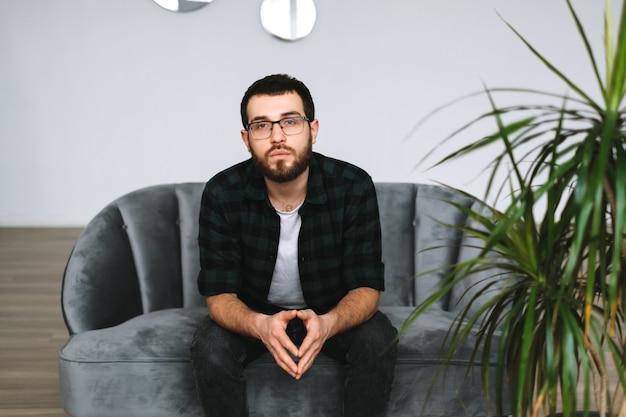 ソファに座っている深刻な白人男性の肖像画