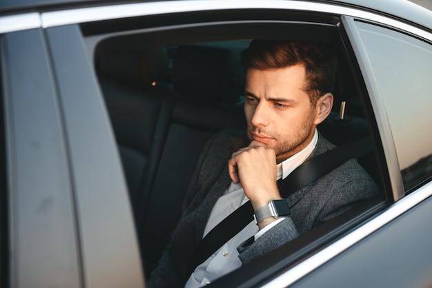 Портрет серьезного кавказского человека, одетого в деловой костюм, сзади, сидя во время езды в машине с ремнем безопасности