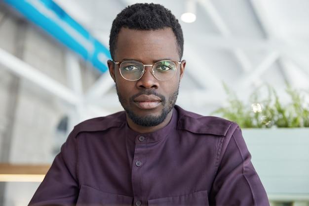 眼鏡とフォーマルなシャツ、黒い肌の深刻な自信を持って男性会社員の肖像画が広々としたキャビネットでポーズします。