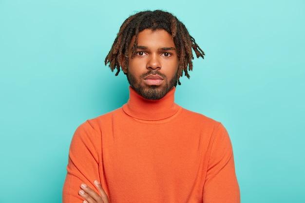 真面目な自信のある男性の肖像画は、健康な黒い肌、恐怖とあごひげを持っており、カメラをまっすぐ見て、物思いにふける表情をしています
