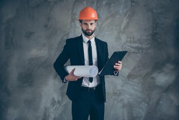 심각한 자신감 남자 작업자 건축가 보류 청사진 클립 보드의 초상화는 회색 벽 위에 절연 빌더 작업 착용 검은 유행 턱시도 턱시도를 구성하려는 프리미엄 사진