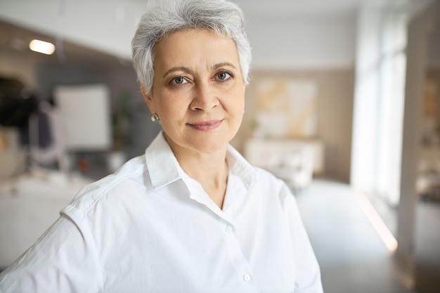 Портрет серьезной уверенной в себе женщины средних лет с седыми короткими волосами, зелеными глазами, морщинами и очаровательной улыбкой позирует в помещении со скрещенными руками