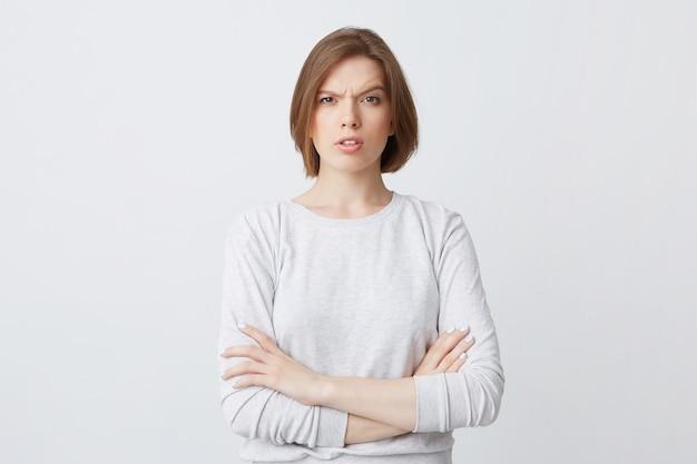 腕を組んで立っている長袖の深刻な混乱している若い女性の肖像画と混乱して探して