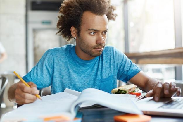 大学でファーストフードを食べるクラスの準備の練習帳でノートを書くノートを注意深く見ている深刻な浅黒い肌の学生の肖像画。集中している男性は非常に忙しい