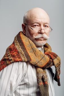 Портрет серьезного пожилого мужчины в очках на сером