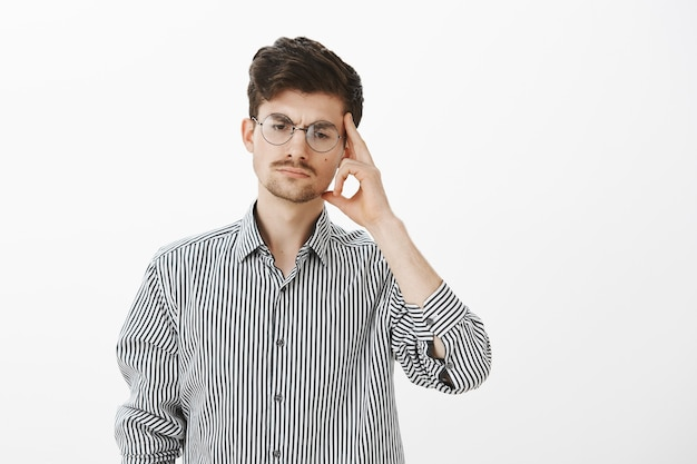 丸いメガネをかけた深刻な集中男性同僚の肖像、人差し指で寺院を見下ろして保持し、考えながら集中し、不快な状況を回避する方法を計画する
