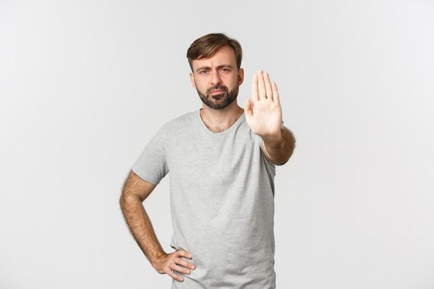 Портрет серьезного хмурого парня в серой футболке