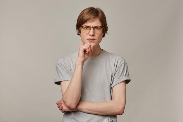 Портрет серьезного, хмурого мужчины со светлыми волосами. в серой футболке и очках. концепция людей и эмоций. касается подбородка и думает.