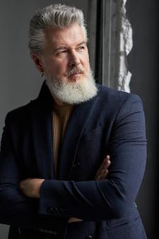 Портрет серьезного седого мужчины средних лет в деловой повседневной одежде, глядя на