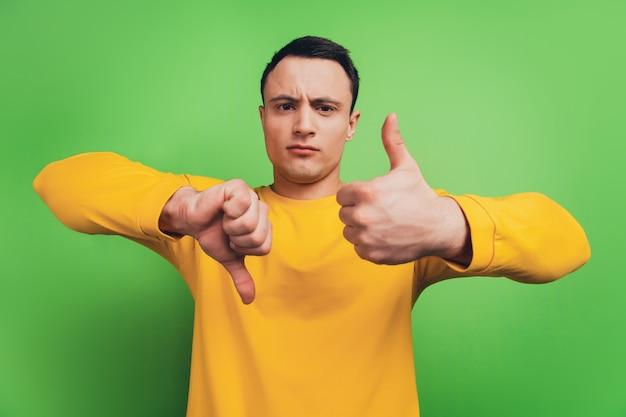 真面目な男の肖像画は親指を上に表示し、緑の背景に解決策を選択します