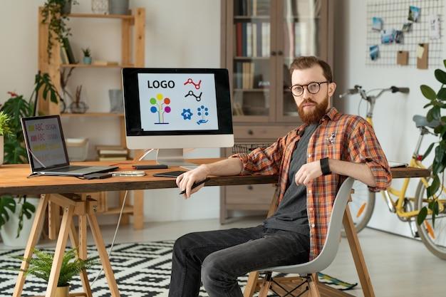 ホームオフィスでデスクトップコンピューターとラップトップと机に座っている真面目なハンサムなひげを生やしたブランドデザイナーの肖像画