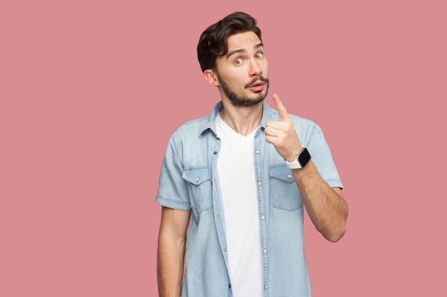 Портрет серьезного красивого бородатого молодого человека в голубой рубашке повседневного стиля, стоящего с согревающим знаком и смотрящего в камеру, чтобы обратить внимание. крытая студия выстрел, изолированные на розовом фоне.