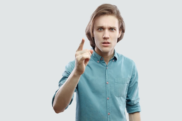 Портрет серьезного красивого длинноволосого белокурого молодого человека в голубой повседневной рубашке, стоящего с предупреждающим знаком и смотрящего в камеру. крытая студия выстрел, изолированные на светло-сером фоне.