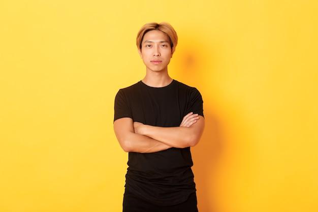 Портрет серьезного уверенного в себе азиатского парня в черной футболке