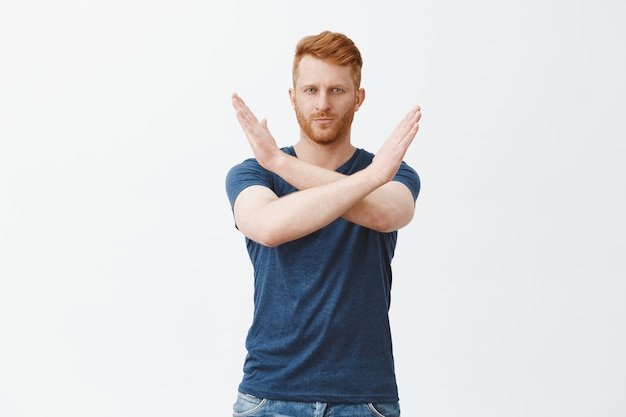 Портрет серьезного зрелого привлекательного рыжего мужчины с щетиной в синей футболке, делающего крест руками возле груди, показывая стоп, достаточно или отказный жест