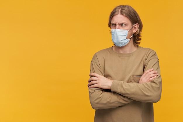 Портрет серьезного мужчины со светлыми волосами и бородой. в бежевом свитере и медицинской маске. держит руки скрещенными. наблюдая за осуждением слева в пространстве для копирования, изолированном над желтой стеной