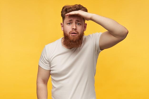 빨간 머리와 수염을 가진 심각한 남성의 초상화, 빈 티셔츠를 입고 이마 옆에 손바닥을 잡고 거리를 응시합니다.
