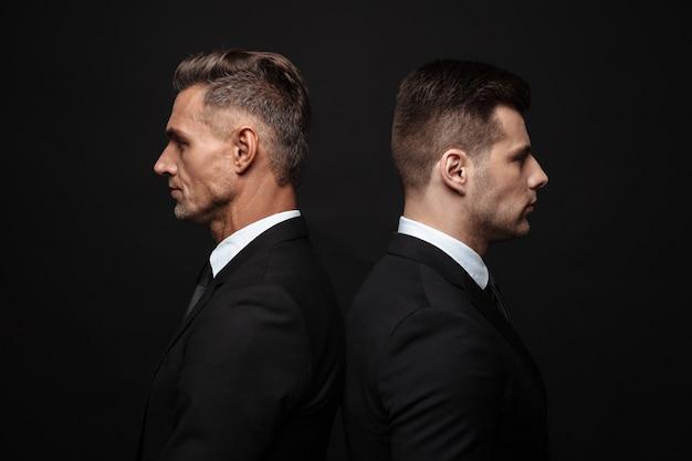 Портрет серьезных мужественных двух бизнесменов, одетых в строгий костюм, позирующих перед камерой спина к спине, изолированные на черной стене
