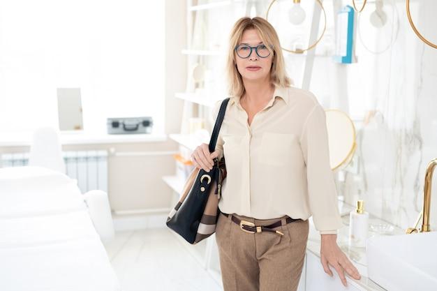 아름다운 미용사 방에서 어깨에 가방과 함께 서 안경에 심각한 성숙한 blond-haired 여자의 초상화