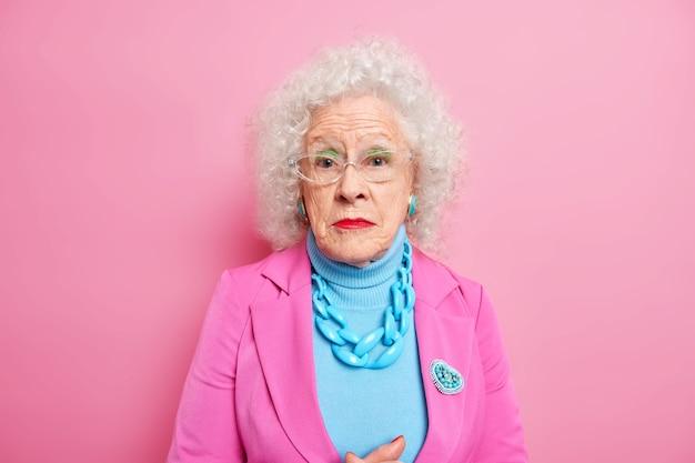 Портрет серьезной зрелой седой женщины, одетой в элегантную одежду с украшениями, носит макияж, остается красивым, несмотря на ее старость, позирует в помещении у розовой стены. модная бабушка