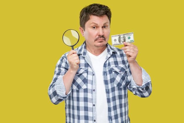 立って、お金を持って、光学ガラスを拡大し、カメラを見ているカジュアルな市松模様のシャツを着た真面目な中年の検査官ビジネスマンの肖像画。スタジオショット、黄色の背景に分離。