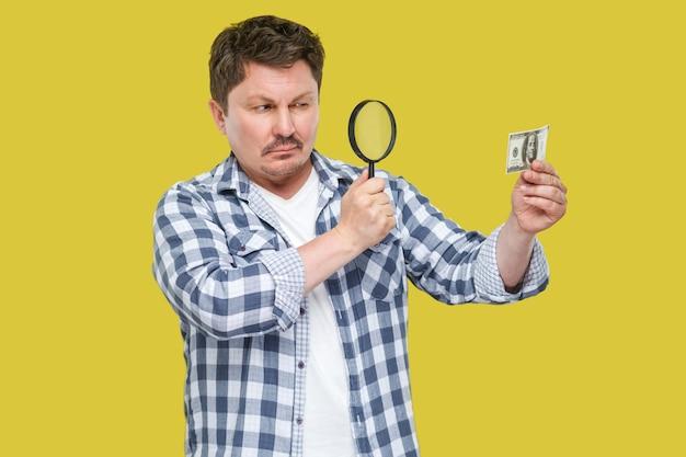拡大鏡の光学ガラスで立って、持って、お金を見ているカジュアルな市松模様のシャツを着た真面目な中年の検査官のビジネスマンの肖像画。黄色の背景に分離された屋内スタジオショット。