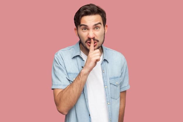 Портрет серьезного или сердитого бородатого молодого человека в голубой рубашке повседневного стиля, стоящего с жестом знака молчания, пальцем на губах и смотрящим в камеру. крытая студия выстрел, изолированные на розовом фоне.