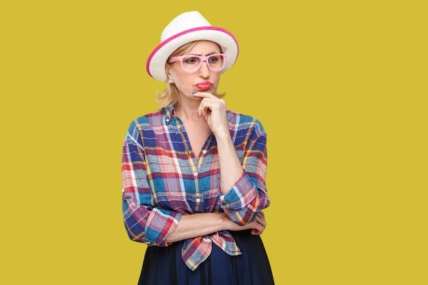Портрет серьезной задумчивой современной стильной зрелой женщины в повседневном стиле с шляпой и очками, стоящей, глядя в сторону и сомневающейся в раздумьях. крытая студия выстрел, изолированные на желтом фоне.