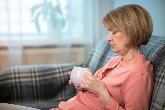 심각한 슬픈 잠겨있는 사려 깊은 여자, 차 또는 커피 한잔과 함께 노인 수석 여자의 초상화
