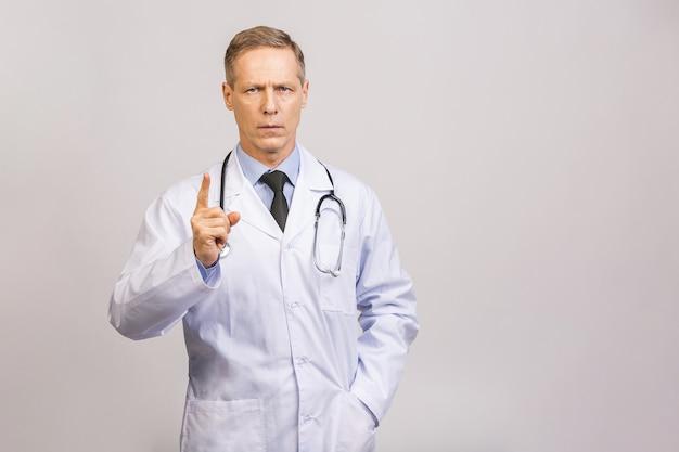 灰色の壁に孤立した笑みを浮かべて深刻な年配の男性医師の肖像画。