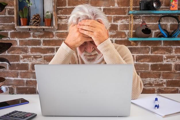 Портрет серьезного старшего человека, использующего портативный компьютер в домашнем офисе. кирпичная стена в фоновом режиме