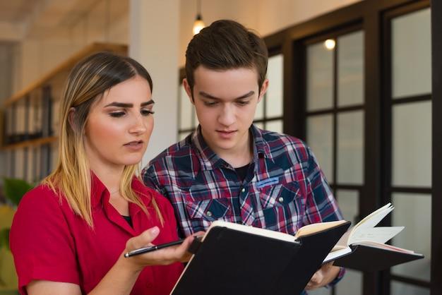 Портрет серьезного студенческого мальчика и девушки обсуждают лекцию