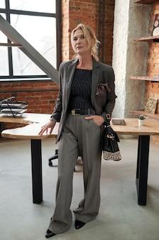 자신의 현대 사무실에서 책상에 가방과 함께 서있는 회색 정장에 심각한 세련된 성숙한 아가씨의 초상화