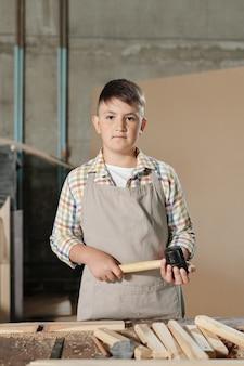 木工店で木の板と机にハンマーで立っているエプロンの深刻な10代の少年の肖像画