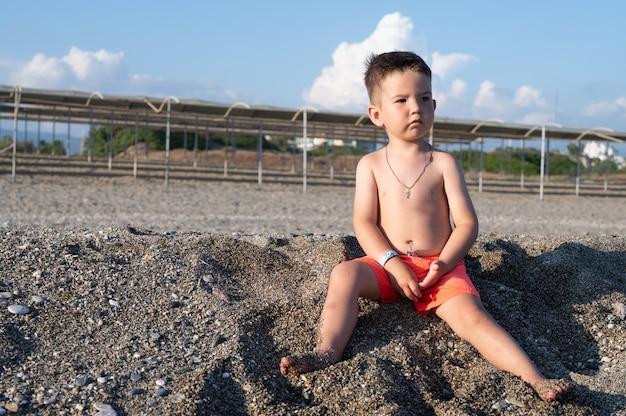 빈 해변에서 노는 심각한 유아 소년의 초상화.