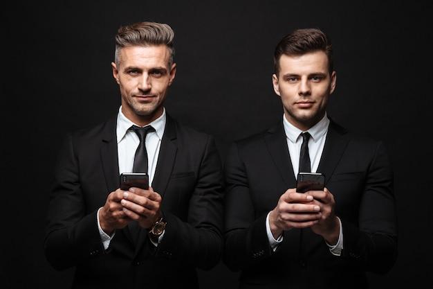 Портрет двух серьезных бизнесменов, одетых в строгий костюм, позирует перед камерой с мобильными телефонами, изолированными над черной стеной
