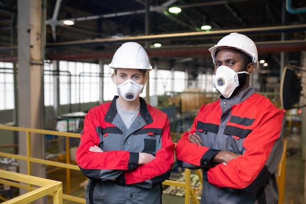 Портрет серьезных рабочих в респираторных масках и касках, стоящих со скрещенными руками на каркасном мосту в заводском цехе
