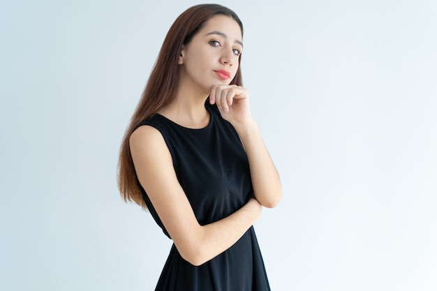 Портрет серьезной молодой азиатской коммерсантки стоя в сомнении