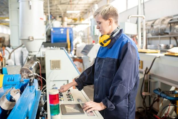 Портрет серьезной молодой азиатской женщины, надевающей защитные перчатки на руки в мастерской по металлообработке