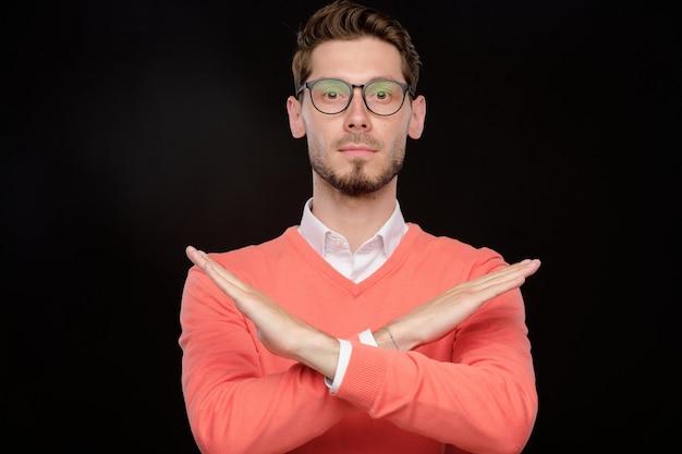 黒の孤立した背景に対して拒否ジェスチャーをする眼鏡の深刻な若いひげを生やした男の肖像画
