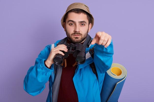 Портрет серьезного молодого европейского туристического парня с сумкой и биноклем, изолированным на сиреневом фоне