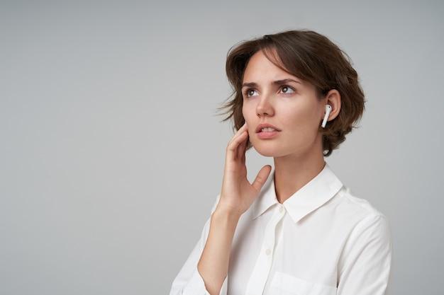 짧은 머리가 그녀의 뺨에 손바닥을 들고 위쪽으로 신중하게보고 포즈를 취하는 동안 흰색 셔츠를 입고 심각한 젊은 여성의 초상화