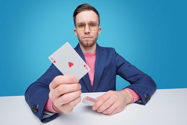 テーブルに座ってエースカードを示すジャケットの真面目な若いギャンブラーの肖像画