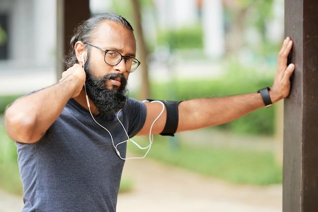 야외에서 훈련하는 동안 이어폰으로 음악을 들으며 수염을 기른 진지한 인도 주자 초상화