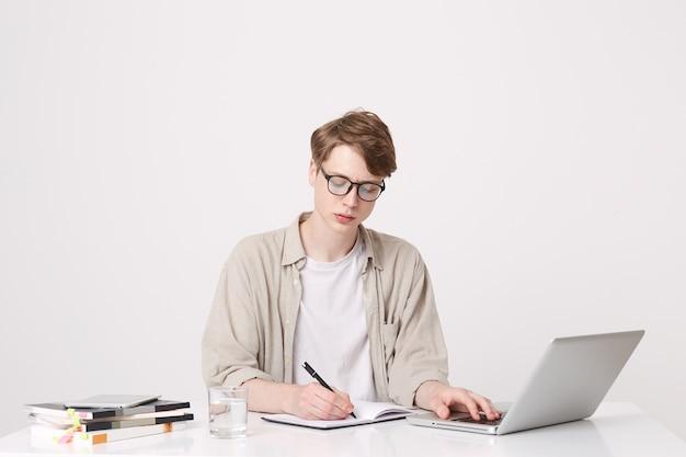 Портрет серьезного молодого человека-студента в бежевой рубашке и очках пишет и учится за столом, используя портативный компьютер и ноутбуки, изолированные на белой стене