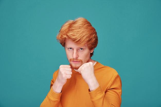 ボクシングの位置に立って、身を守る準備ができているひげを持つ深刻な若い赤毛の男の肖像画