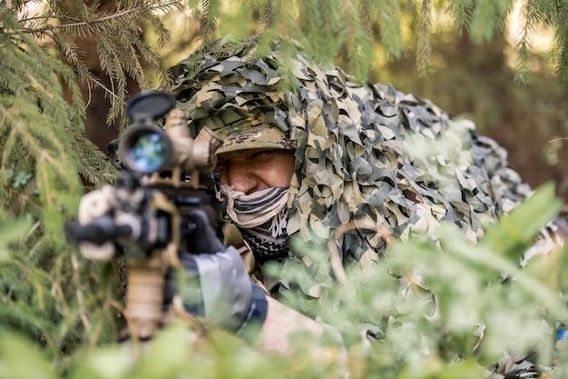 숲 나무에 무기를 들고 서 있는 위장 복장을 한 진지한 젊은 군인의 초상화