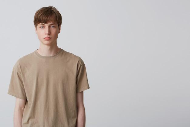 あなたの広告のためのコピースペースで白い壁の上に隔離されたベージュのtシャツを凝視し、身に着けている真面目な若い学生の肖像画